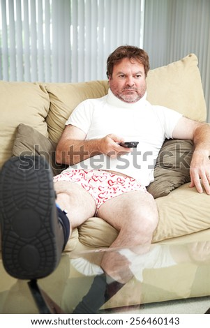 Injured man at home on the couch, wearing a foot brace and neck collar.   - stock photo