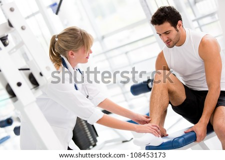 Injured man at the gym feeling pain in his ankle - stock photo