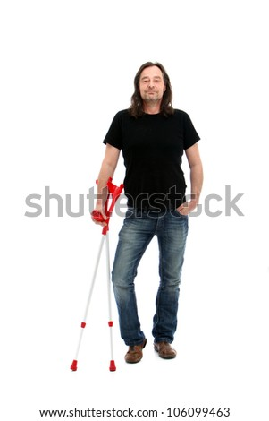 Injured middle-aged man standing holding a pair of crutches as he smiles his satisfaction with the way in which his rehabilitation is progressing - stock photo