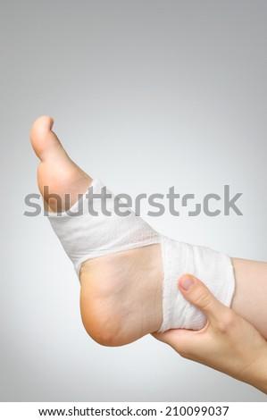 Injured painful foot with white gauze bandage - stock photo