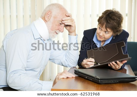 Injured senior man and his accountant worrying about the cost of medical bills. - stock photo