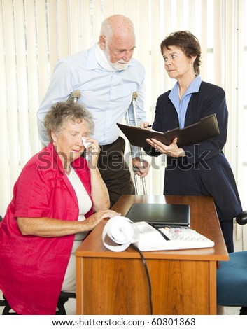 Injured senior man and his upset wife meet with a personal injury lawyer. - stock photo
