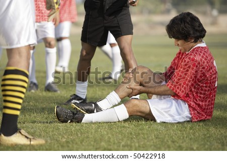 Injured soccer player sitting on pitch, portrait - stock photo