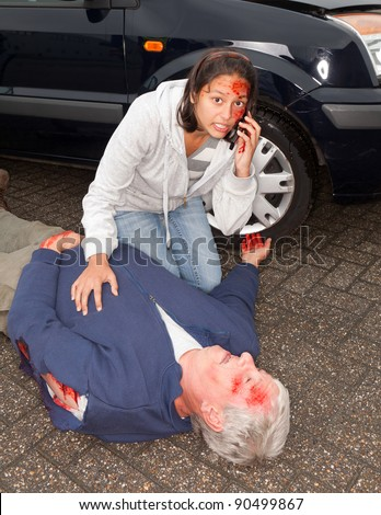 Injured woman calling for an ambulance after a car accident - stock photo