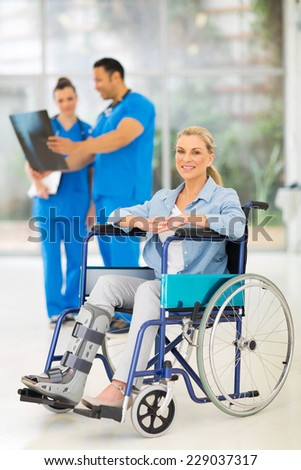 injured woman on wheelchair with doctors at medical office - stock photo