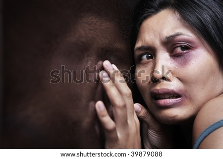 Injured woman terrified, leaning on the wooden wall. Concept for domestic violence - stock photo