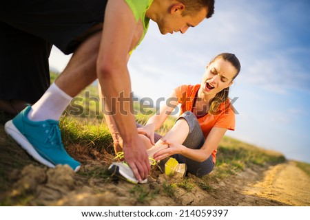 Injury - sports woman with twisted sprained getting help from man touching her ankle. - stock photo