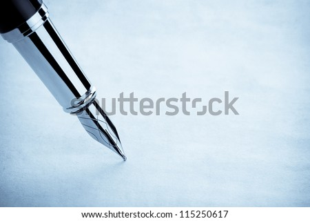 ink pen and parchment background - stock photo