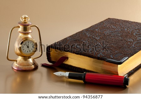 Ink red pen, vintage bronze clock and notepad with reflex - stock photo