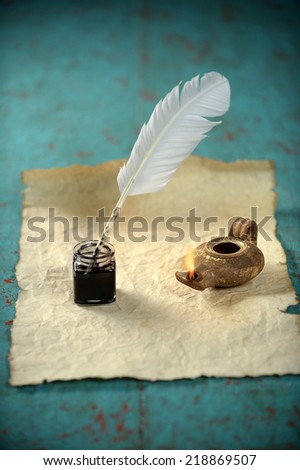 Inkwell and ancient lamp over paper on vintage table - stock photo