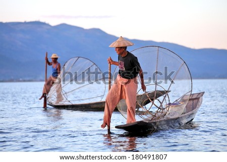 INLE LAKE, MYANMAR DECEMBER 12, 2013: Fishermen at Inle Lake, Shan State, Myanmar Intha people possess the leg-rowing style and the unique coop-like fishing equipment - stock photo
