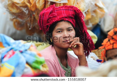 INLE LAKE, MYANMAR, SEPTEMBER 5: An unidentified Burmese woman with thanaka on her face on September 5, 2013 in Inle Lake, Myanmar. Thanaka is a yellowish-white cosmetic paste made from ground bark. - stock photo