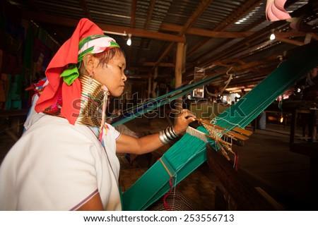 INLE,MYANMAR-SEP 29 : Unidentified  Padaung ( Karen or Kayan Lahwi ) woman wearing the traditional metal rings around her neck,working at a weaving in village on September 29,2014,Inle lake,Myanmar. - stock photo