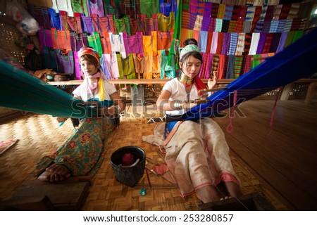 INLE,MYANMAR-SEP 29 : Unidentified two Padaung ( Karen or Kayan Lahwi ) girl wearing the traditional metal rings around her neck,working at a weaving in village on September 29,2014,Inle lake,Myanmar. - stock photo