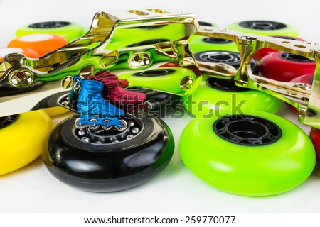 Inline skate wheels with reflection in gold inline skate frames and keychain in the shape of roller shoes - stock photo