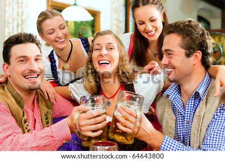 Inn or pub in Bavaria - group of five young men and women in traditional Tracht drinking beer and having a party with beer - stock photo