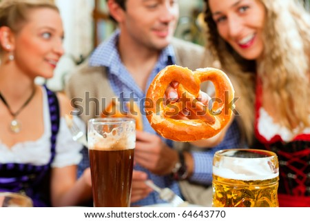 Inn or pub in Bavaria - group of young men and women in traditional Tracht drinking beer and eating pretzel - stock photo