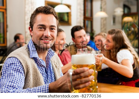 Inn or pub in Bavaria - man in traditional Tract drinking beer - stock photo
