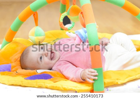 Innocent baby smiling and playing with toys - stock photo