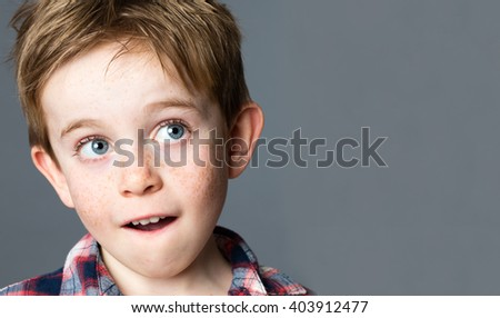 innocent thinking - closeup portrait of a beautiful red hair preschool kid with freckles looking up to daydream and imagine, copy space on grey background studio - stock photo
