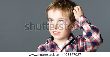 innocent thinking - closeup portrait of a sweet red hair little boy looking up, scratching his head for idea and imagination, copy space on grey background studio