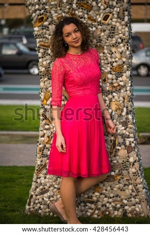 Innocent young woman in pink dress - stock photo