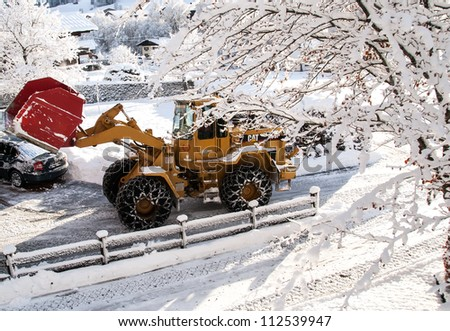 INNSBRUCK; AUSTRIA - JAN 08: Snow removal vehicle removing snow after blizzard which caused several damages on the streets of Innsbruck in Tirol, Austria on January 08, 2012. - stock photo