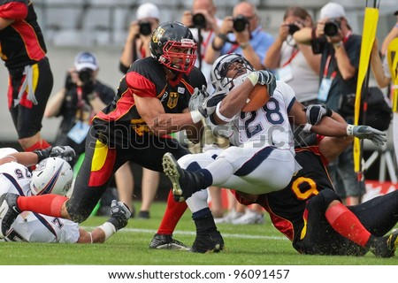 INNSBRUCK, AUSTRIA - JULY 10: RB Da'Shawn Thomas (#28 USA) is tackled at the Football World Championship on July 10, 2011 in Innsbruck, Austria. USA wins 48:7 against Germany. - stock photo