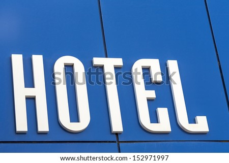 Inscription hotel on blue wall, the entrance to the hotel. - stock photo