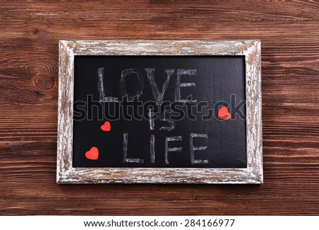 Inscription LOVE IS LIFE on blackboard on wooden background - stock photo