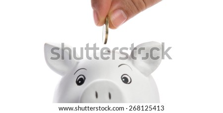 insert coin in a piggy bank, isolated on white - stock photo