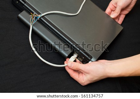 insert to repair the power cord into the computer - stock photo