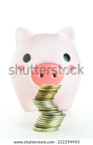 Inserting a coin into a piggy bank - stock photo