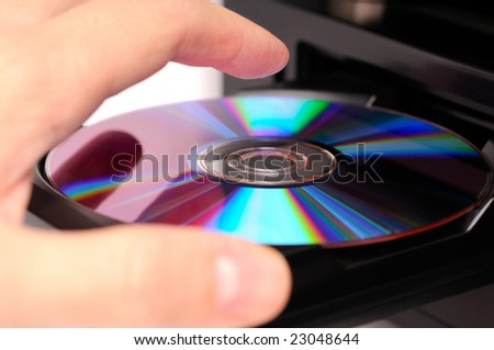 Inserting a disc into a DVD or CD player - stock photo