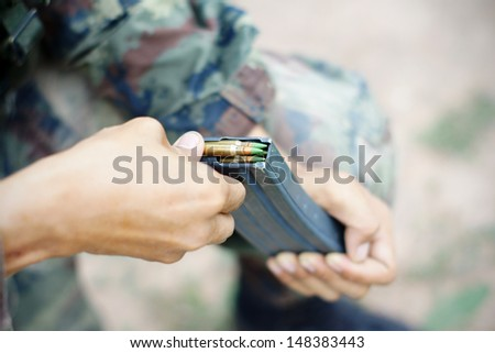 inserting ammunition into the cartridge - stock photo