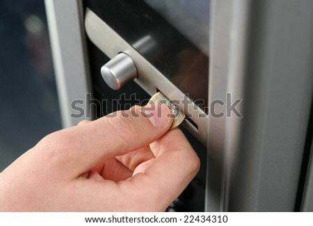 inserting coin in to a vending machine - stock photo