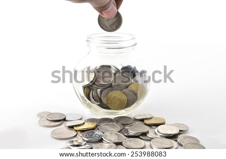 Inserting Malaysian Coin in glass container. Shoot over white background. Focus on the important part. Shallow depth of field. - stock photo