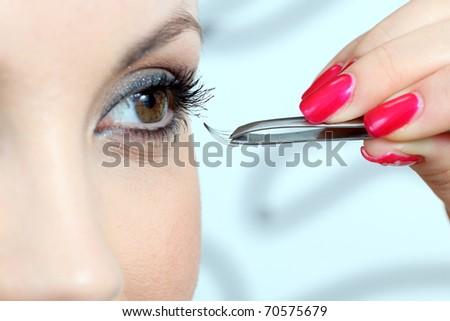 Insertion of false eyelashes. Close up. - stock photo