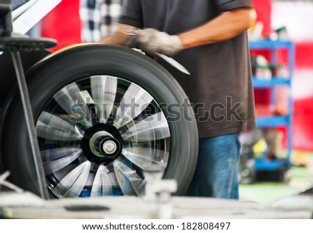 Inside a garage - changing wheels-tire during spinning wheel - stock photo