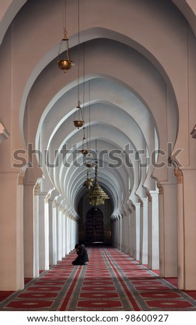 Inside a mosque with muslim man kneeling praying - stock photo