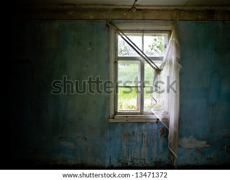 Inside abandoned house. View on broken window with curtain. Grunge scene. - stock photo