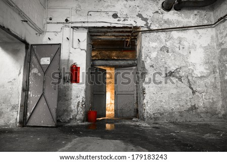 inside an old industrial building, basement, open door - stock photo