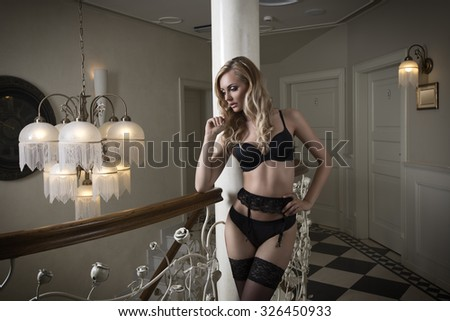 inside portrait of very sexy blonde woman with black lingerie and stockings, posing in elegant luxury hotel ambient  - stock photo