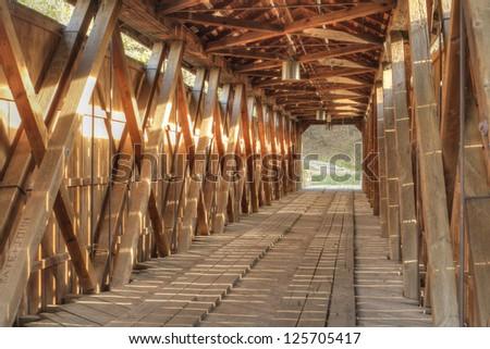 Inside sunlit covered bridge - stock photo