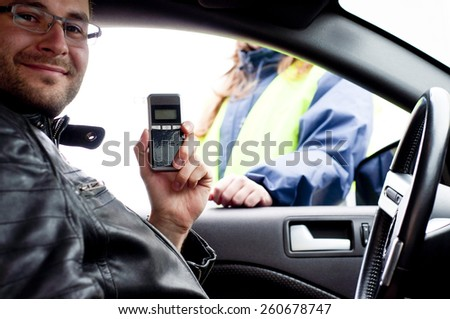 Inside the car view of a young drink and drive driver due to being subject to test for alcohol content with use of breathalyzer, happy as he is all clear - stock photo
