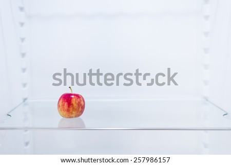 inside the fridge, single apple on shelf - stock photo