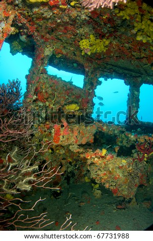 Inside the wheel house of an old tug, all surfaces encrusted with coral growth. - stock photo