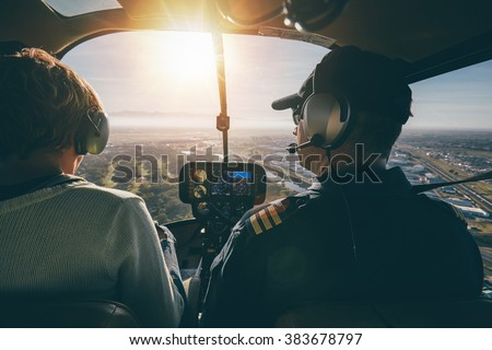 Inside view of a helicopter in flight, with man and woman pilots flying a helicopter on a sunny day. - stock photo