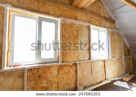 Inside wall heat isolation with mineral wool in wooden house,  building under construction  - stock photo