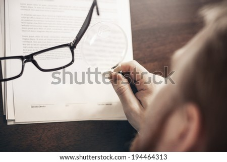 Inspecting Agreement with Magnifying Glass - stock photo
